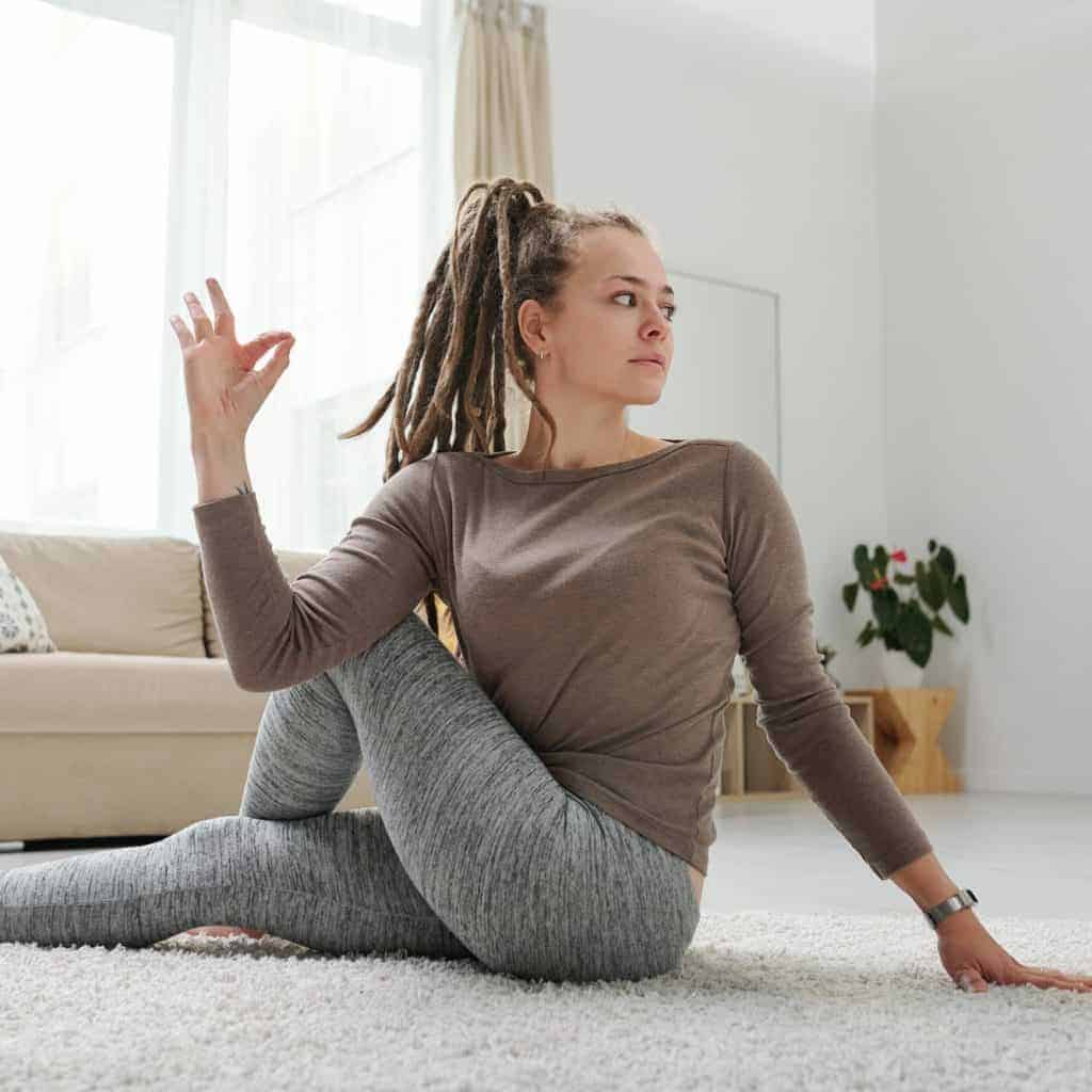 Young female with dreadlocks sitting on the floor in one of yoga positions