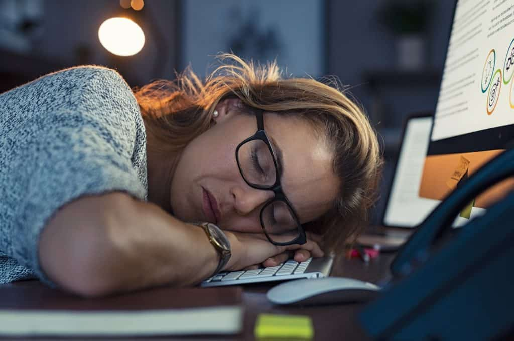Business woman sleeping on computer at night